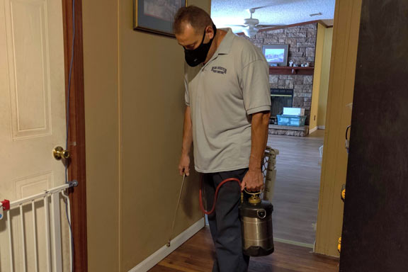 Steve at Ron Shuster Pest Control Spring Hill spraying inside home in Hudson Florida